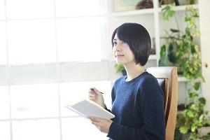 ノートをp持つ女性