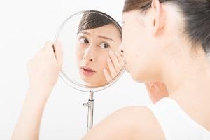 お肌を気にして鏡を見る